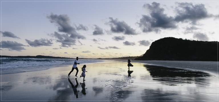 family running on beach at dusk